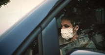 woman wearing a face mask driving a car