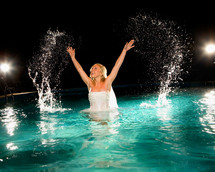 bride splashing in a pool