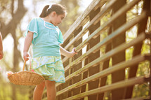 girl child holding a basket looking over the rails on a bridge