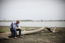 A young man praying while sitting on a log next to a lake bed.