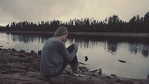 woman sitting by the edge of a lake