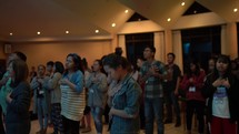 people swaying and praying during a worship service