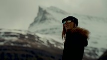 a woman standing in front of a snow covered mountain peak
