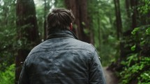 a man hiking on a forest trail