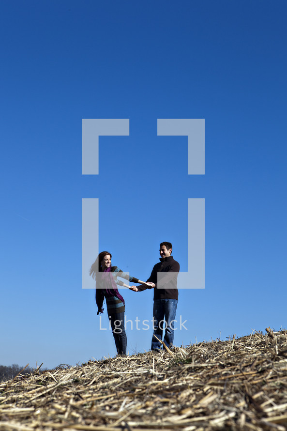 playful couple on top of a hill
