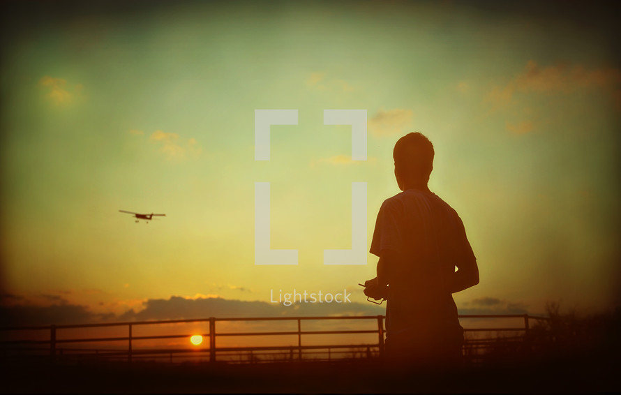 Boy flying remote-controlled airplane
