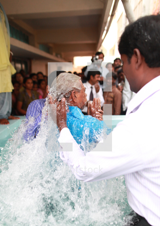 man being dunked during a baptism in India