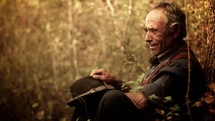 an old man sitting outdoors thinking