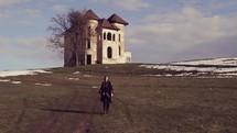 a person in a cape walking near a castle