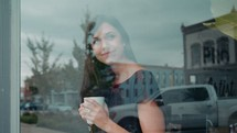 a woman holding a coffee cup and looking out a window