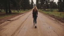 woman walking down a dirt road