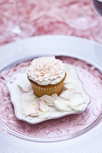 ornately decorated cupcake pink on plate with floral petals