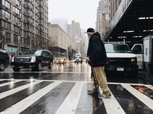 an elderly man with a cane using a crosswalk on a rainy day