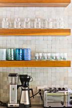 Kitchen wood shelf with appliances blender, coffee maker, toaster, mason jars, cups, glasses, tile back splash