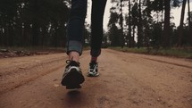 feet of a woman walking down a dirt road