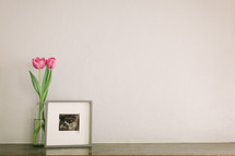 pink tulip in a vase and a framed picture