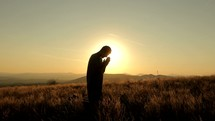 a man kneeling in prayer on a mountaintop at sunset