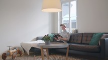 A man sitting on a couch in front of a window reading a Bible