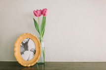 A vase of pink tulips next to a framed photo of a mother and newborn baby.