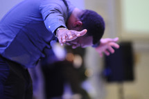 man with outstretched arms bowing
