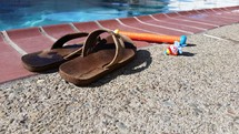flip flops and dive stick on the edge of a pool