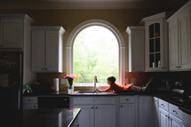 a little girl lying on a kitchen counter