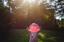 a little girl holding up a paper stop sign