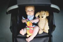an infant and teddy bear in a stroller