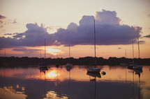 sunset reflected across water and sailboats