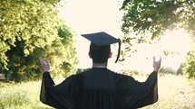 a graduate walking forward and raising hands to praise God and pray