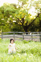 dark hair toddler girl playing in tall green grass field with fence yellow dress