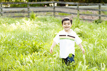 boy child playing in tall green grass field