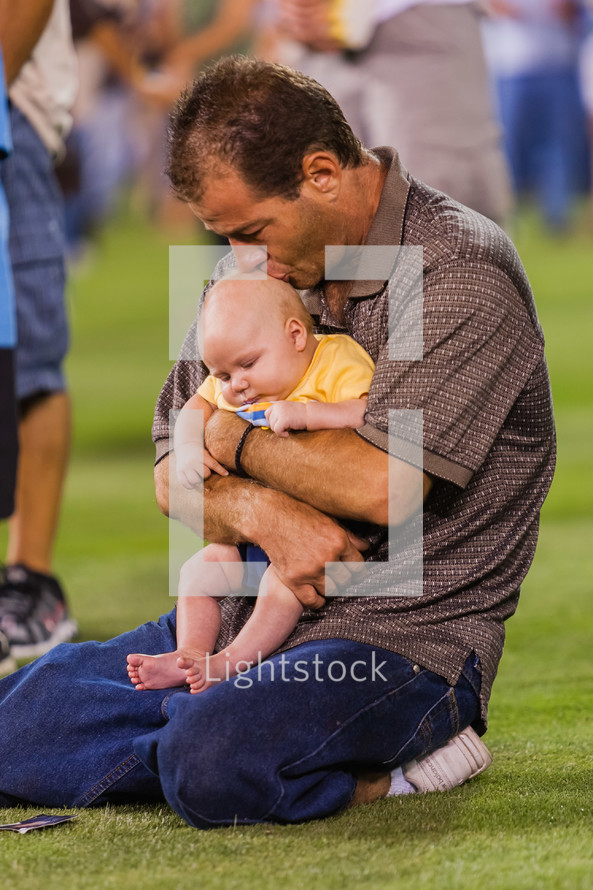 Man holding an infant child on knees praying at a crusade