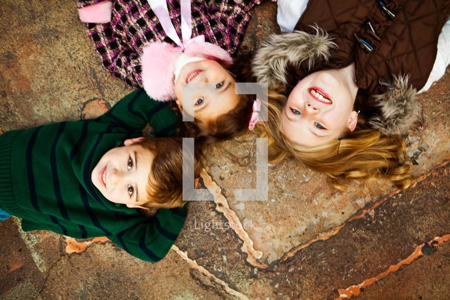 Kids lying down smiling