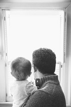 father and toddler son looking out a window