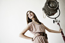 young woman standing next to a spotlight