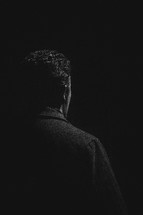 Back of a man in the dark.