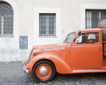 an old orange truck parked on a cobblestone street in Rome