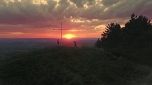 praying by a cross on a mountain top at sunset