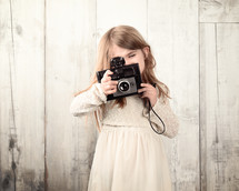 A little girl holding a vintage camera