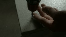 using a power screwdriver to screw into metal