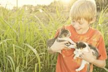 Boy holding kittens in a field