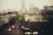 A blurry view of a city through a rain covered window