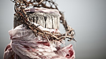 A crown of thorns and a blood-soaked garment hang from a wooden beam.