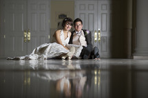 bride and groom sitting on a marble floor