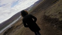 a woman walking up a dirt path