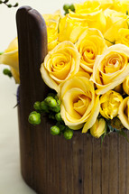 Flower arrangement yellow roses in wood vase basket