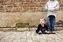 Siblings on cobblestone road