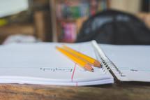 School pencils on a spiral notebook at a school desk.