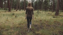Back of woman walking through the trees in the woods.